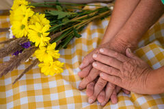 Hands of senior couple. Bouquet on checkered cloth. Best gift of fate. I'll take care of you Royalty Free Stock Photo