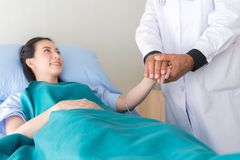 Hands senior man doctor reassuring her female patient in hospital room,Doctor giving a consultation and encouragement to patient,H royalty free stock photography