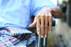 Hands of senior man sitting on bench in home. hands clasped togethe stock photo
