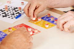 Hands of senior people playing Bingo Stock Image