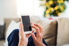 Hands of senior woman with smartphone at Christmas time. Copy space. stock image