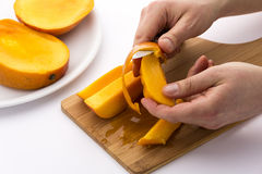 Hands Separating Mango Fruit Flesh From Its Skin Stock Image