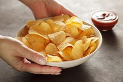 Hands serving bowl with potato chips on table with dip sauce. Woman giving crispy snacks Stock Photos