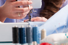 Hands on sewing machine with reels of colour threads and sewing Royalty Free Stock Images
