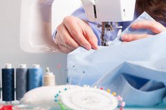 Hands on sewing machine with reels of colour threads and sewing Royalty Free Stock Image