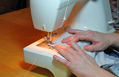 Hands sewing with a machine. Stock Photos