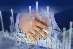 Hands shaking over money and financial graph. Business Men's hands shaking over bulk of money and financial graph on blue background - Financial success concept Royalty Free Stock Photography