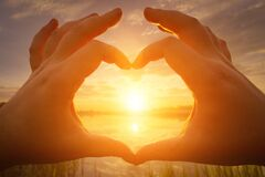 Hands in the shape of heart against the sunset