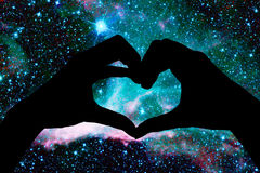 Hands in the shape of a heart, starry night. Background Royalty Free Stock Photos