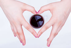 Hands shaped in heart around coffee Royalty Free Stock Images