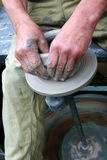 Hands shaping clay on potter's wheel. Hands shaping clay pot on potter's wheel Stock Photography