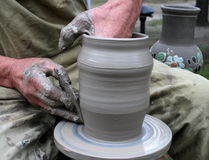 Hands shaping clay on potter's wheel. Hands shaping clay pot on potter's wheel Royalty Free Stock Photo