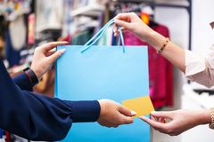 Hands with shopping bag and credit card close up. Stock Image