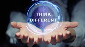Hands show round hologram Think different. Female hands show a round conceptual hologram with text Think different. Unrecognizable woman in ashen white on a stock footage
