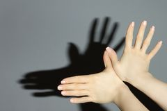 Hands show a shadow of bird. On gray background Stock Photo
