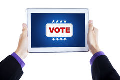 Hands show tablet with vote button Royalty Free Stock Photo