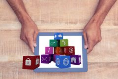 Hands showing icons on the screen of one tablet computer against wooden background Royalty Free Stock Images