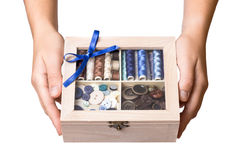 Hands showing sewing box. Pretty female hands show wooden sewing box Royalty Free Stock Photo