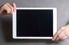 Hands showing tablet. A tablet is a wireless touch screen personal computer that is smaller than a notebook but larger than a smartphone royalty free stock photo