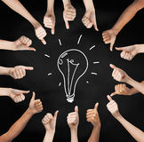 Hands showing thumbs up in circle over bulb symbol Royalty Free Stock Images