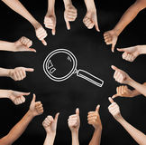 Hands showing thumbs up in circle over magnifier Stock Photos