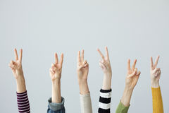 Hands showing victory sign on grey background Royalty Free Stock Image