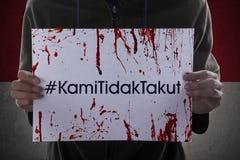 Hands shows hashtag Kami Tidak Takut Stock Photography
