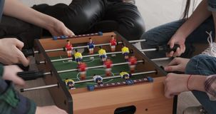 Hands of children playing foosball. Hands of siblings playing foosball together at home stock video footage
