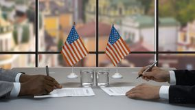 Hands signing papers at table. Handshake of businessmen near flags. Treaty of cooperation. Two american politicians stock footage