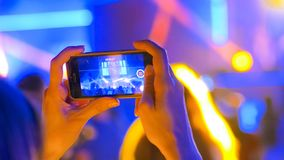 Hands silhouette recording video of live music concert with smartphone. Unrecognizable hands silhouette taking photo or recording video of live music concert stock photos