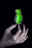 Hands in silver paint holding light green feather Stock Image