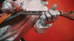 Hands in silver rubber gloves of hazard suit playing balalaika in red room. Hands in silver rubber gloves of man in hazard suit playing russian native musical stock footage