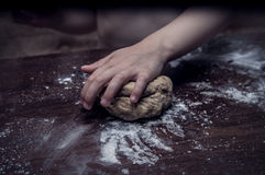 Hands skillfully knead the dough Stock Images