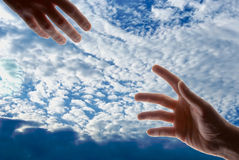 Hands in the sky. Two male hands with fingers outstretched reaching out toward each other stock photo