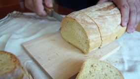 Hands slice loaves of bread. Close up stock video