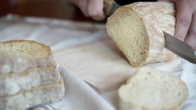 Hands slice loaves of bread. Close up stock video footage