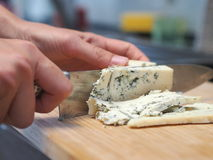 Hands slicing blue cheese. With a knife stock photos