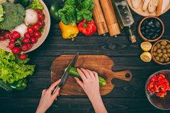 Hands slicing cucumber by knife. Top view of cropped hands slicing cucumber by knife on chopping board with vegetables Stock Photo