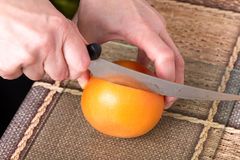 Hands slicing grapefruit with knife. Hands slicing grapefruit with knife on a table as a background Royalty Free Stock Photography