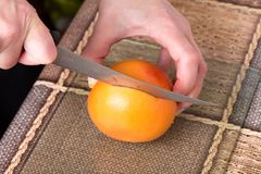 Hands slicing grapefruit with knife. Hands slicing grapefruit with knife on a table as a background Stock Photography