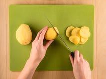 Hands slicing potatoe on green plastic board. Hands holding knife and slicing potatoe on green plastic board, simple food preparation illustration, vegetarian Royalty Free Stock Photo
