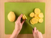Hands slicing potatoe on used plastic board. Hands holding knife and slicing potatoe on used plastic board, simple food preparation illustration, vegetarian Royalty Free Stock Image