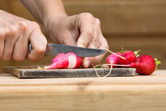 Hands slicing radishes on the wooden cutting board. Hands of woman slicing radishes on the wooden cutting board Stock Photography