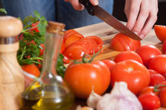 Hands  slicing tomatoes at table Royalty Free Stock Photos