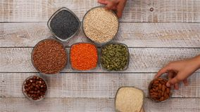 Hands slide in whole grains in bowls diversified diet concept
