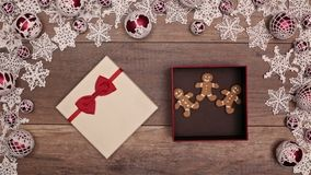 Hands slipping a christmas present box inside a seasonal decorations frame. Opening to reveal gingerbread cookies people stock footage