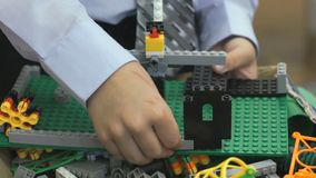 Hands of an unknown boy playing with building kit stock video