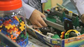 Hands of an unknown boy playing with building kit stock video footage