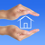 Hands With Small House. On blue background stock photo