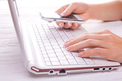 Hands with smart phone and computer keyboard Royalty Free Stock Photos